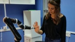 Photo: Student researcher Shir Kashi interacts with robotic arm; Copyright: Ben-Gurion U. Israel