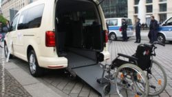 Photo: Inklusion taxi with opened tailgate and an attached ramp with a wheelchair on it; Copyright: InklusionsTaxi/Herbert Schlemmer