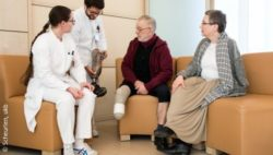 Photo: Dagmar Marth in a consultation situation with a patient and other medical staff; Copyright: Scheurlen, ukb