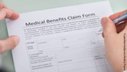 Photo: Close-up of a person filling in a hand over medical benefits claim form; Copyright: panthermedia.net/Andriy Popov