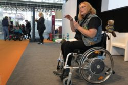 Photo: Andrea Schütt in her Wacken wheelchair during her lecture at TREFFPUNKT REHACARE; Copyright: beta-web/Wackerbauer