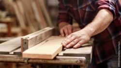 Photo: Male cutting a wooden plank with a circular saw in a workshop; Copyright: PantherMedia/mavoimages