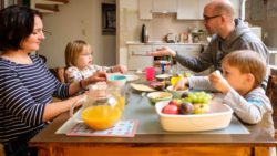 Photo: A family (mother, father and two kids) at the breakfast table; Copyright: Andi Weiland | Gesellschaftsbilder.de