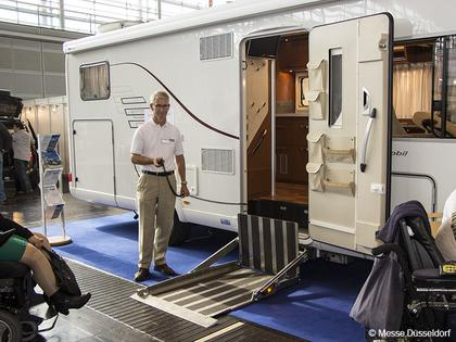 Photo: Man standing next to caravan.