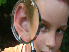 Photo: Magnifying glass over a ear of a child