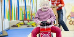 Photo: A girl is riding a toy car; Copyright: Messe Düsseldorf