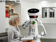 Photo: Service robot gives a rose to a woman