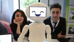 Image: Two researchers are sitting next to a small white robot; Copyright: ScienceRELATIONS