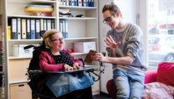 Photo: Talk between two employees in the office. One of them is using a wheelchair; Copyright: Andi Weiland | www.gesellschaftsbilder.de