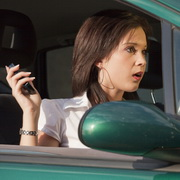 Photo: Teenage girl with cell phone in car, looking shocked