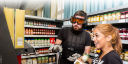 "Photo: Two trainees in the educational venue (""Lernladen"") with simulation goggles and simulation gloves in front of a product shelf; Copyright: EUKOBA e.V."