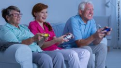 Photo: Older couple playing with a caregiver at the console; Copyright: panthermedia.net/photographee.eu