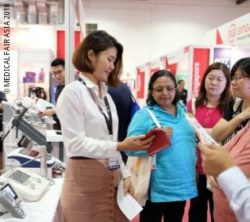 Photo: Exhibitor at MEDICAL FAIR ASIA 2018 talks to interestest visitors of the trade fair; Copyright: MEDICAL FAIR ASIA 2018