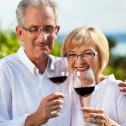 Photo: Elderly man and woman drinking red wine
