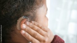 Photo: Close up of a girl of color with a hearing aid; Copyright: panthermedia.net/belchonock
