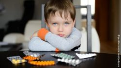 Photo: A boy and lots of pills in front of him on a table; Copyright: panthermedia.net/djedzura