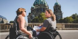 Photo: A man and a woman in wheelchair looking at a street map; Copyright: visitBerlin, Andi Weiland | Gesellschaftsbilder.de