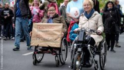Photo: Two women in a wheelchair during a demonstration. One woman holds a sign saying: Participation does not need skills; Copyright: Andi Weiland | Gesellschaftsbilder. de