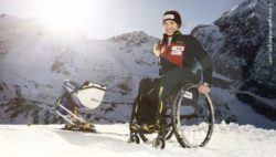 Photo: Anna Schaffelhuber with her monoski in front of a mountain panorama; Copyright: www.panzenberger.com