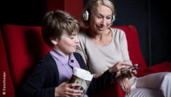 Photo: senior in cinema with her grandson using hearing App
