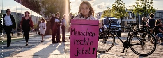 Photo: Woman of short stature on the edge of a demonstration holding a sign with the inscription on it: Human rights now!; Copyright: Andi Weiland | Gesellschaftsbilder.de