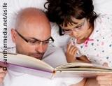 Photo: Father reading to his daughter