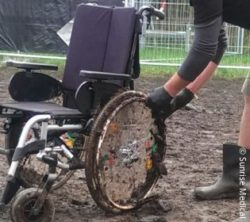 Photo: Service station employee frees a wheelchair from mud on the wheels; Copyright: Sunrise Medical