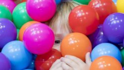 Photo: A child's face can be seen between many colourful balls in a ball pool