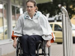 Photo: Wheelchair user with a poncho driving up a ramp; Copyright: Klaus von Kassel