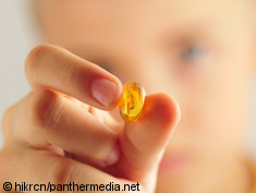 Photo: Boy holding an omega 3 pill in his hand