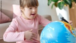 Photo: Girl with trisomy 21 looking at a globe; Copyright: panthermedia.net/AllaSerebrina