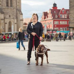 Photo: Nadine Wettstein with her guide dog Lisa at the market square Halle; Copyright: Patrik Bablo