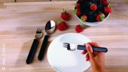 Image: Hand holds a fork, rgonomically contoured utensils and strawberrys behind; Copyright: etac GmbH