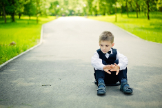 Photo: Lonely child sitting on the ground