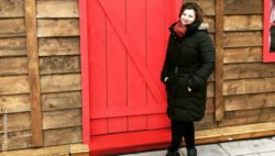 Photo: Claudia Grimm standing in front of a red door; Copyright: Claudia Grimm