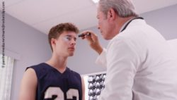 Photo: Physician checking a basketball player's eyes with flashinglight; Copyright: panthermedia.net/mark@rocketclips.com