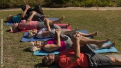 Image: A group of older men and women is lying on a lawn in a gymnastics posture; Copyright: PantherMedia/Wavebreakmedia (YAYMicro)