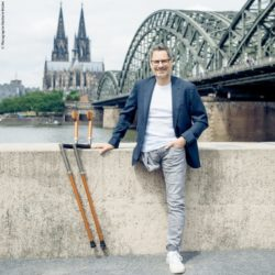 Photo: Dr. Thomas Frey casually leaning against a wall, his walking aids beside him; Copyright: Photographie Nathalie Michel
