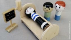 Photo: A hospital situation with a patient lying in bed and connected to a monitor, represented by small wooden puppets; Copyright: Kingston University, London