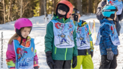 Image: Four children with skiing gear are standing in a snowy forest; Copyright: FIS and World Para Snow Sports