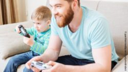 Photo: Little boy playing a video game with his father at the console; Copyright: panthermedia.net/Vadymvdrobot