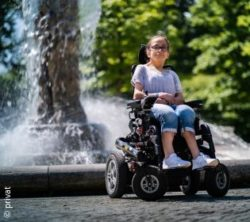 Photo: SmooVie in her wheelchair in front of a fountain; Copyright: private