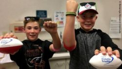 "Image: two boys each raising one arm and holding a small baseball with the inscription ""Diabetes TrialNet"" in their other hand; Copyright: Benaroya Research Institute"