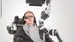 Photo: a man is sitting in a power wheelchair, he is wearing glasses; Copyright: HomeBraceGermany UG