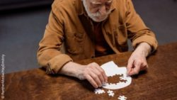 Image: An old man is putting together a jigsaw puzzle that is shaped like a human head; Copyright: PantherMedia/HayDmitriy