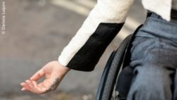 Photo: Arm of a wheelchair user next to the wheelchair wheel. She is wearing a jacket with special fabric on the sleeve; Copyright: Daniela Luquini