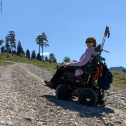 Photo: Woman in power wheelchair X8 in the mountains during the ascent, she looks slightly over her shoulder into the camera; Copyright: Sunrise Medical