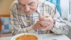 Photo: Elderly man with hand tremor tries to eat some soup; Copyright: PantherMedia/weyo