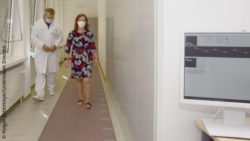 Photo: Patient Sabine H. walking down a corridor together with Prof. Tjalf Ziemssen; Copyright: Holger Ostermeyer/University Hospital Dresden