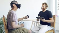 Photo: Georg Teufl during rehabilitation process with a stroke patient using virtual reality glasses; Copyright: Rewellio GmbH